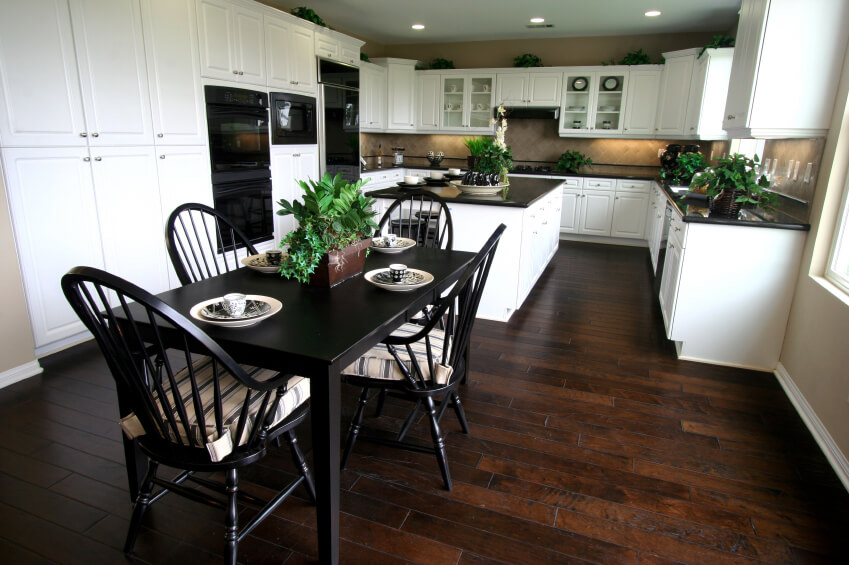 This sprawling kitchen sets pristine white cabinetry over rich, warm toned hardwood flooring, while employing jet black as a counterpoint. Black countertops and a black dining table infuse the space with a jolt of poignant high contrast.