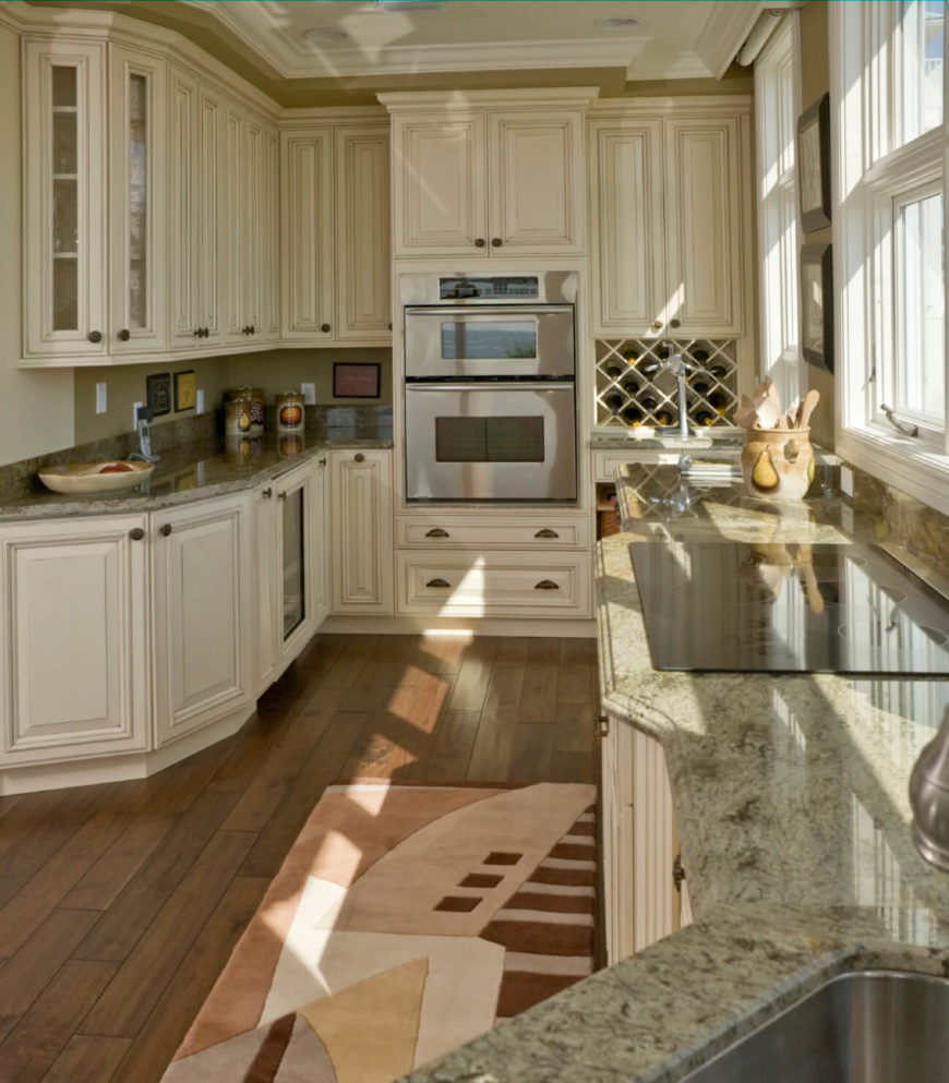This kitchen makes the most of its narrow presence with bold and detailed white cabinetry over dark hardwood flooring, plus light green granite countertops all around. Features such as a built-in wine rack and glass door cabinets add style and function.