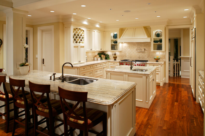 Sensuous hardwood floors grant a warm tone to this bright kitchen, flush with ornate white cabinetry and granite countertops. A pair of islands feature built-in sinks and the larger one hosts space for in-kitchen dining.