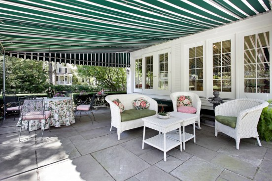 A shaded, quaint cottage style patio with large format flagstone tiles and a green striped awning. A hedge along one side hems in the relaxation area.