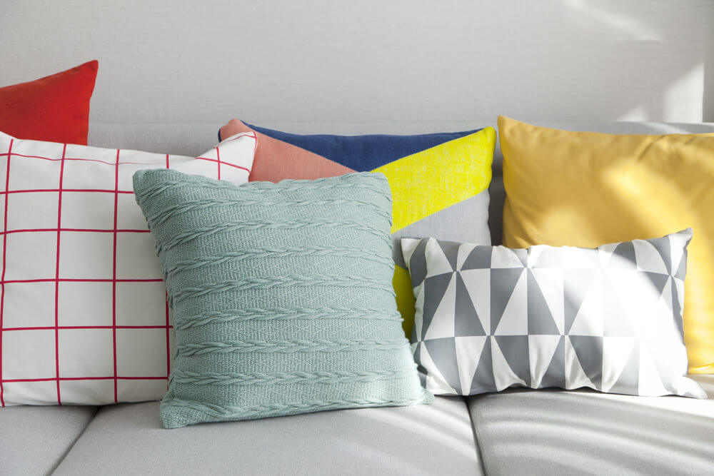 Light grey couch with a diverse mix of throw pillows - solid and geometric patterns along with a mix of colors - white, red, yellow, green and grey.