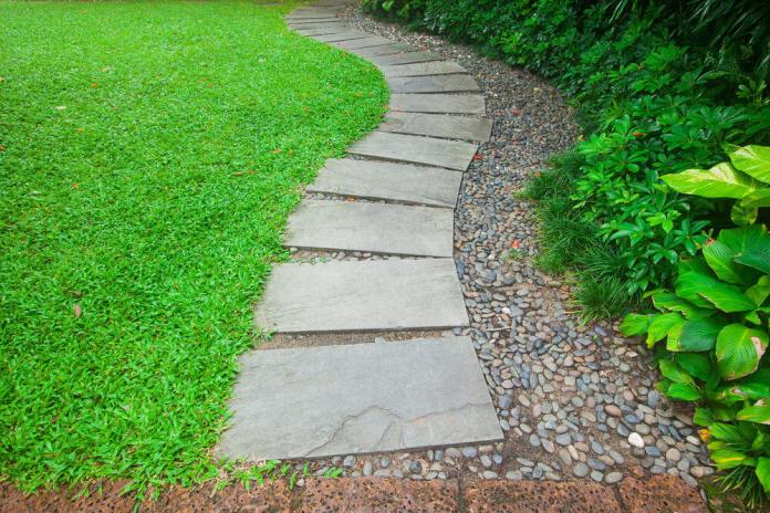 These rectangular pavers laying in a line are edged with grasses on one side while there are stones on the opposite side.