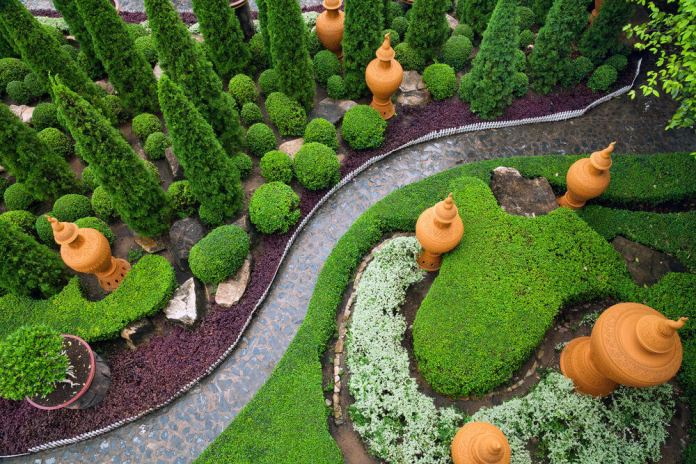 A cool and green bird's eye view of this garden pathway featuring topiary and up-sized pot decors. A flagstone pathway looks beautiful from the upper view.
