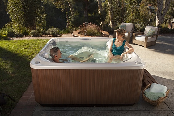 a couple enjoying a soak in a limelight flair spa in a backyard surrounded by forest
