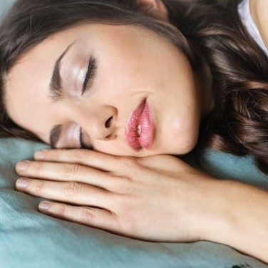 A Woman Laid On Her Side In Bed - Does Sleep Apnea Cause Depression
