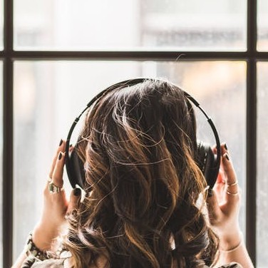 A Lady listening with headphones - Tips To Relieve Anxiety