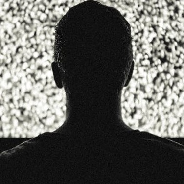 A man staring at white noise on a tv - Stigma of Mental Health