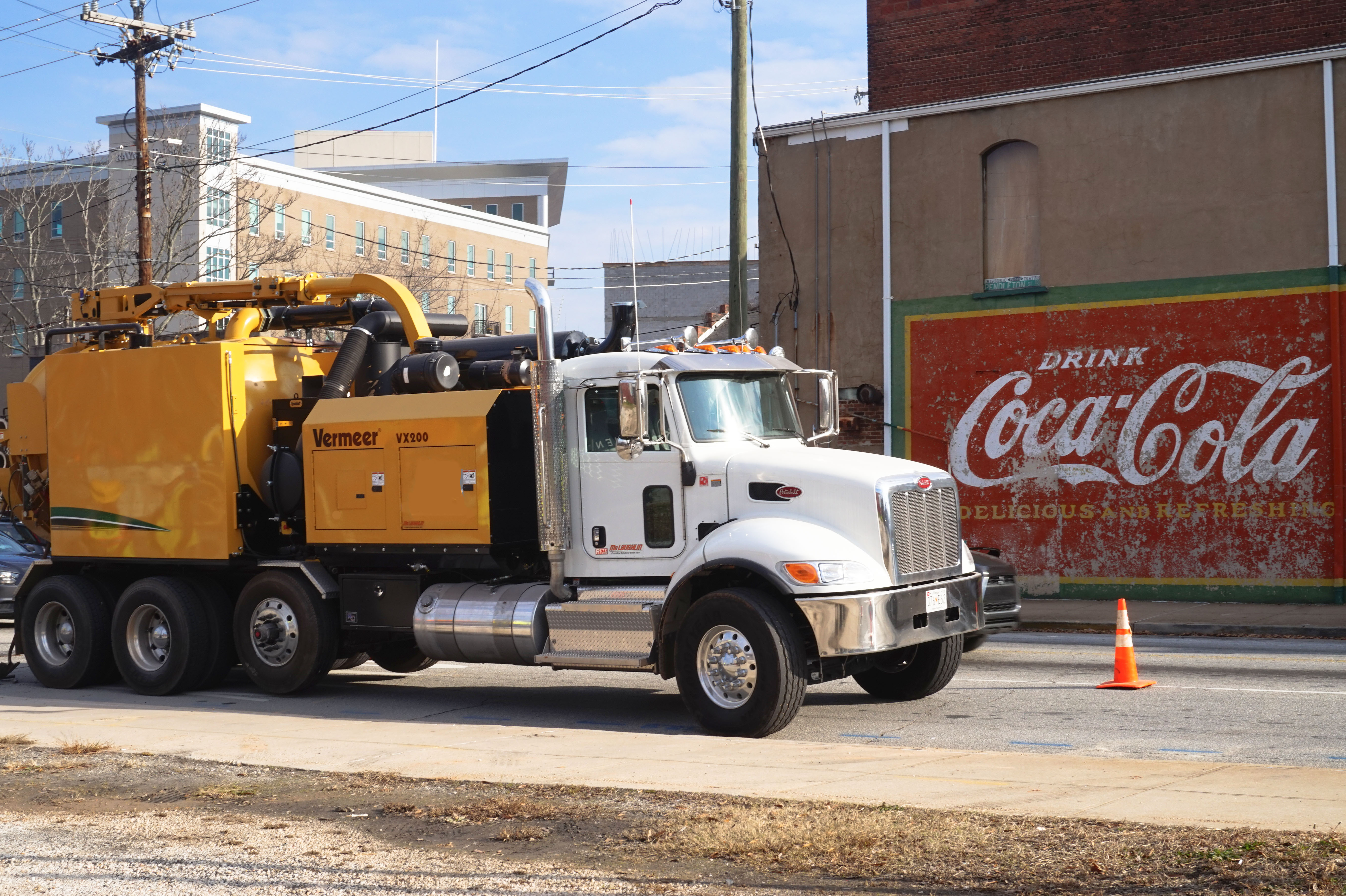 Mega Vacuum excavator in font of coke sign downtown greenville