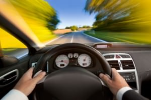 Car interior with man in suit driving fast