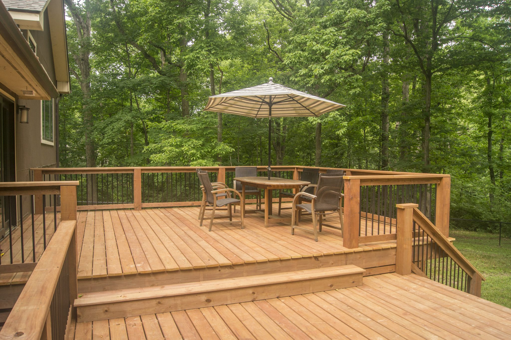 New backyard deck built by TrueSon Exteriors featuring patio furniture.