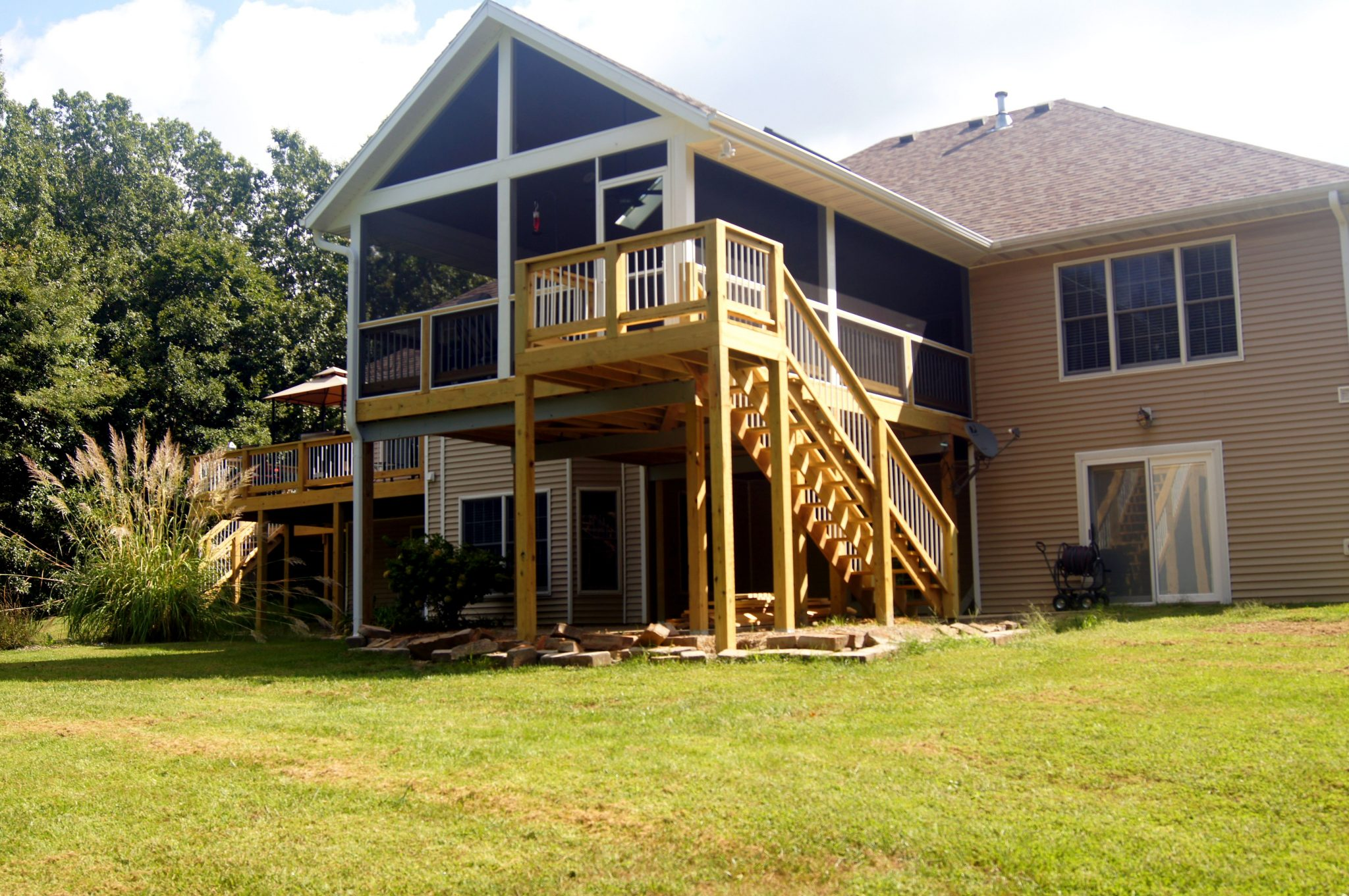 New screened in porch and deck stairs leading to backyard.
