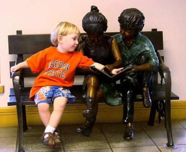 Estatuas de niños leyendo.
