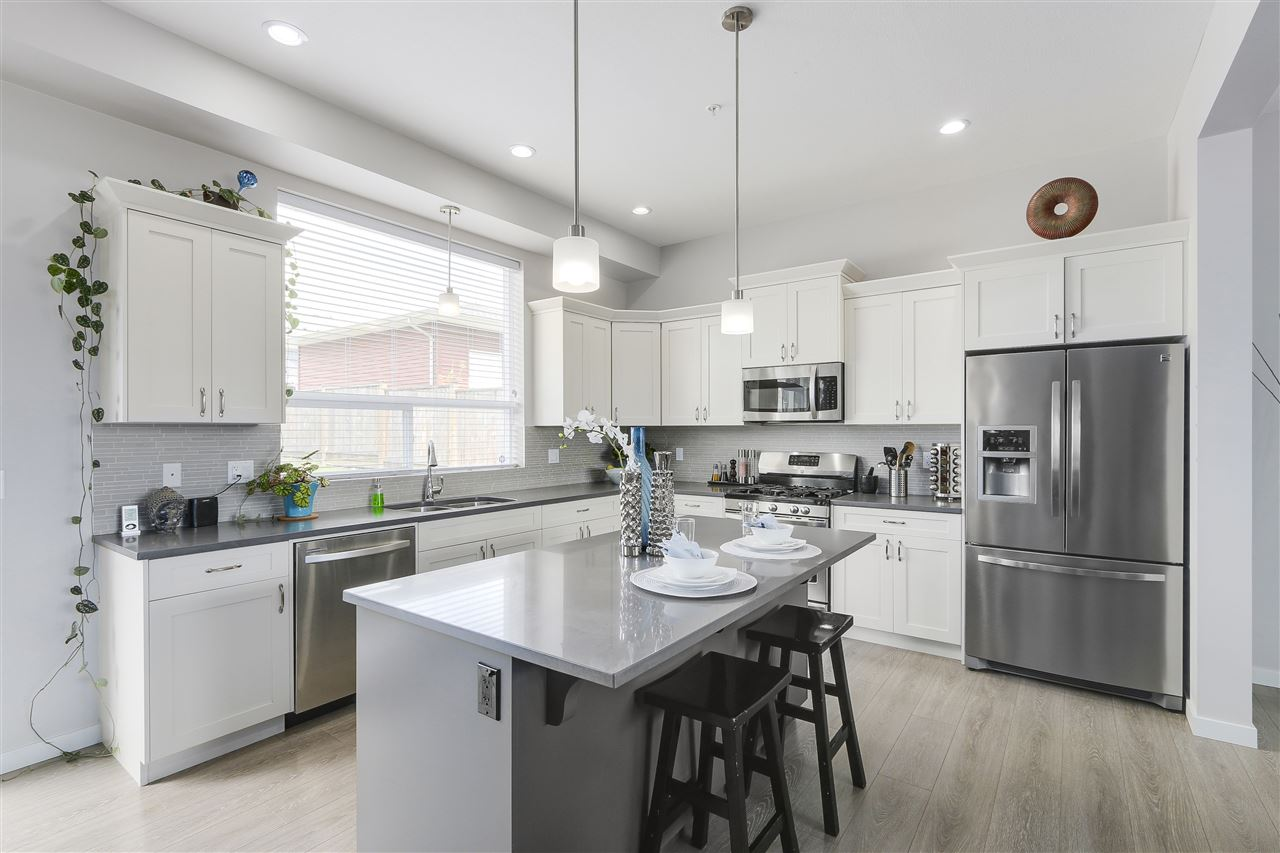 Modern kitchen w/ luxurious quartz stone top, stainless steel appliances ,custom cabinetry, large island w/ eating bar