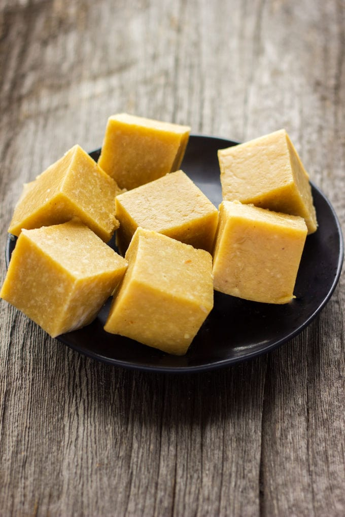This protein-packed, extra smooth and super tasty vegan vanilla fudge recipe is made with only 4 ingredients. Ready under 5 minutes and no-bake, these tiny little protein bars are chewy, fudgy and tastier that anything you will find at the store. Perfect either as a post-workout lunch, quick snack or dessert, they are also entirely refined sugar-free, egg-free, flourless, paleo, dairy-free and gluten-free!
