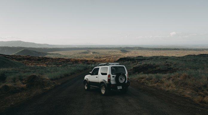 car on dirt road in vast landscape