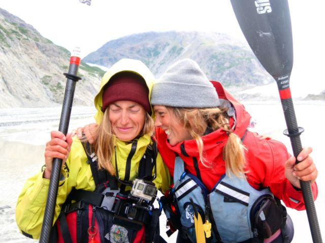 two female paddlers laughing and embracing