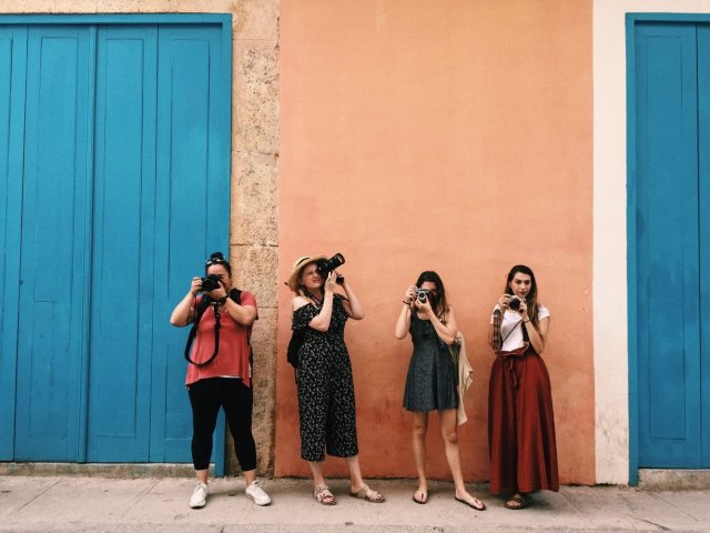 Four female photographers standing against a colorful wall in Latin America