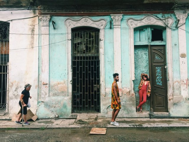 Three pedestrians standing in front of an old turquoise facade