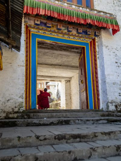 Young monks running up a set of steps and through a colorful doorway