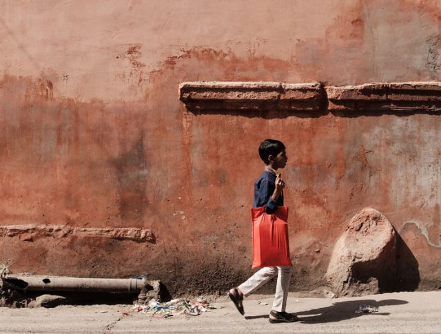 A boy in front of an orange wall in India