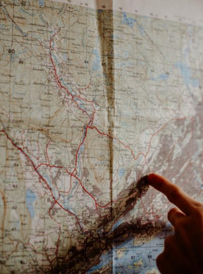 A hand pointing at a map of Norway