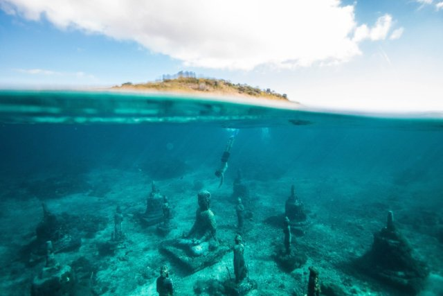 A man snorkeling to an underwater temple in Bali