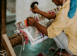 A man weaving textiles at a loom.