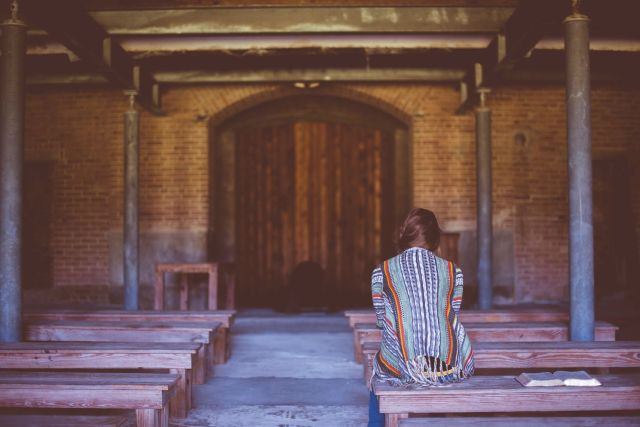 A woman sitting in a wooden church