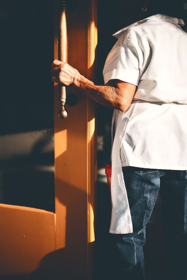 A server opening holding open the door at a restaurant