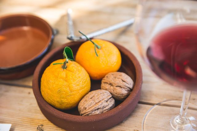 Fresh fruit and nuts sitting in a dish on a wooden table