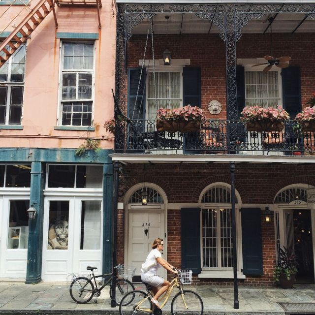 A woman cycling through the streets of New Orleans