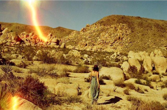 A film photograph of a woman walking through the desert