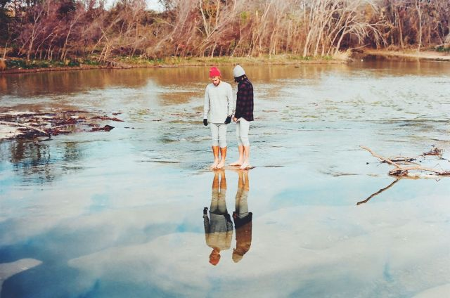 A film photograph of a couple looking at their reflections in a still river