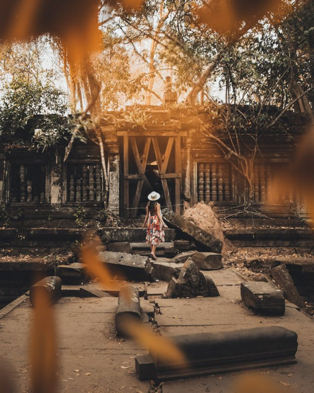 A woman walking through the ruins of a Cambodian temple, seen through yellow leaves in the foreground.