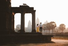 A couple holds hand in the yellow light of sunset at a Cambodian temple.