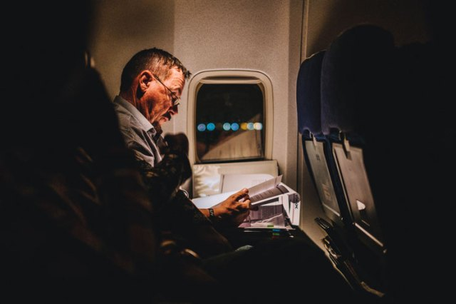 A man reading on a plane at night