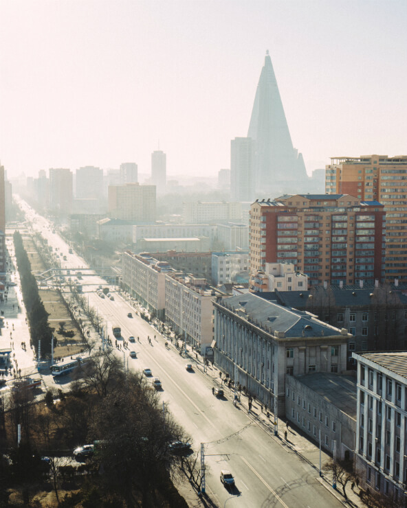 A main road in Pyongyang, North Korea beneath a misty skyline