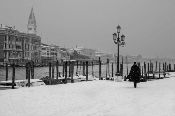 A man walks along a snowy Venice canal