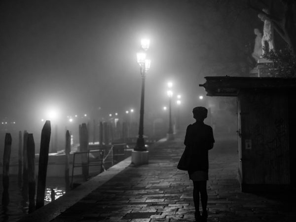 A young boy looks at a lamppost on a Venice evening