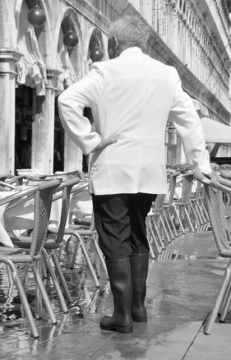 A restauranteur stands among his tables in Venice