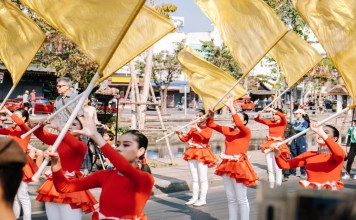 Parade performers twirl yellow flags in the Chiang Mai flower festival.