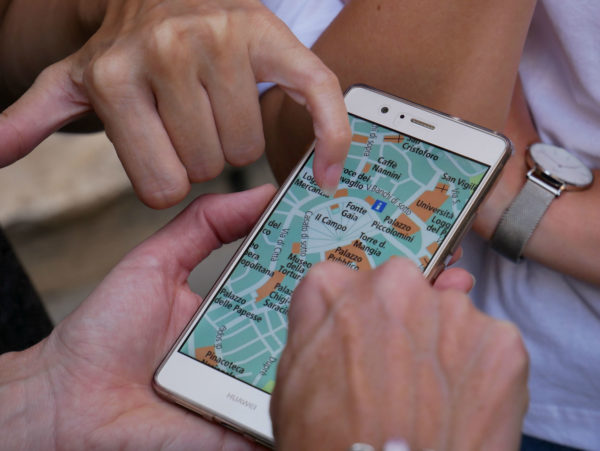 Travelers examine a map on their phone
