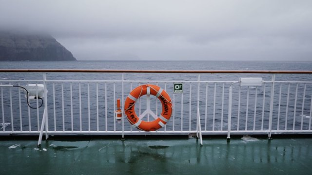 The railing of a ship off the coast of the Faroe Islands