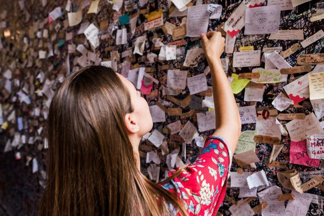 A woman looking a public wall comprised of love letters