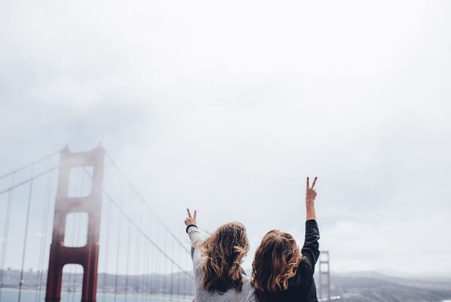 Two people making friends while traveling alone, in front of the Golden Gate Bridge