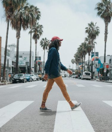 Person strolls across a pedestrian crossing on a palm tree-lined boulevard