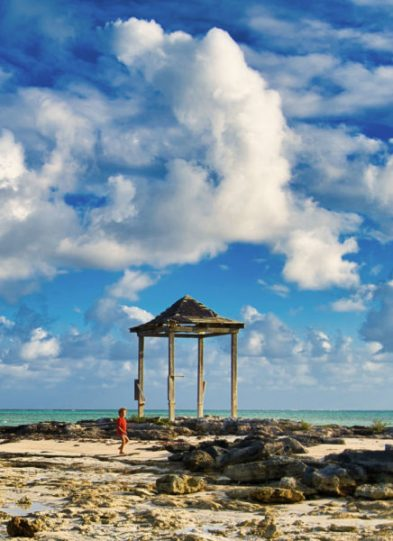 A child walks by a gazebo on a tropical beach