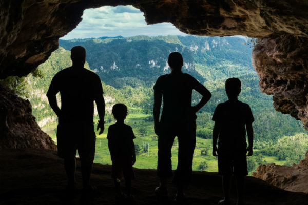 A traveling family looks out at a vista from inside a cave
