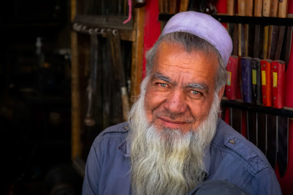 an elderly man in central asia poses in his home.