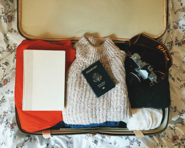 A suitcase neatly packed with sweaters, a camera, and a passport